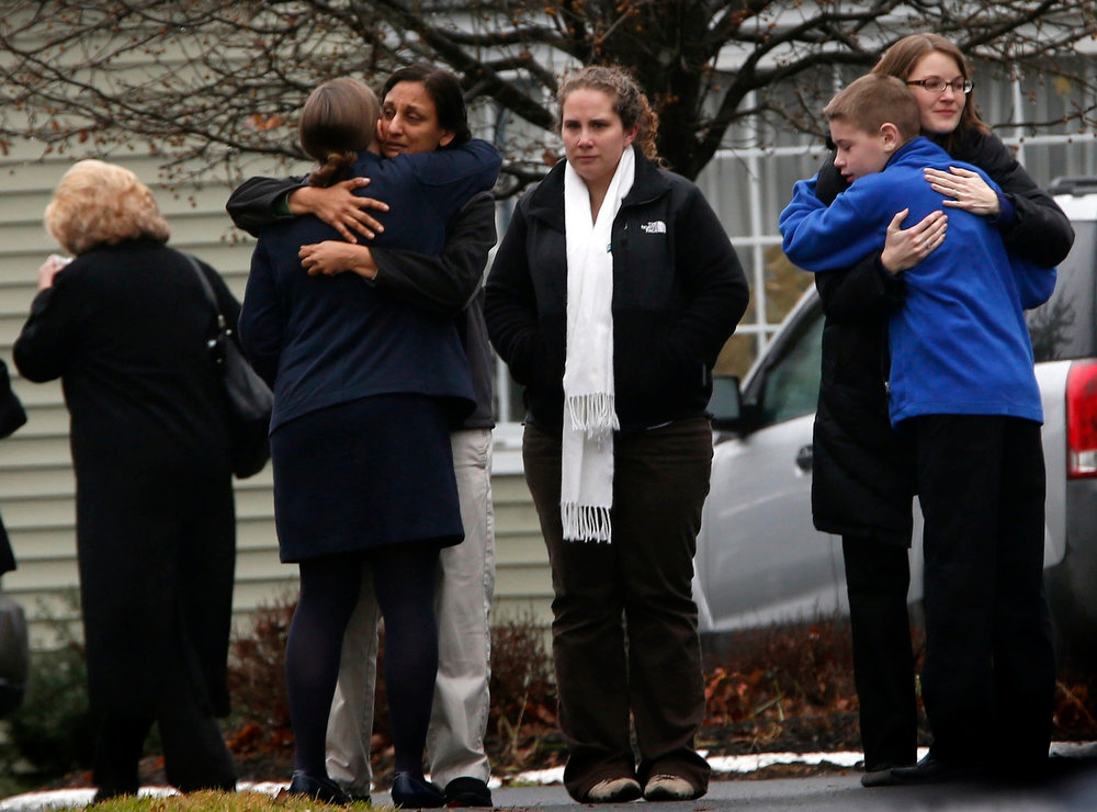 . People embrace outside Honan Funeral Home, where the family of six-year-old Jack Pinto was holding his funeral service, in Newtown, Connecticut December 17, 2012. Pinto was one of 20 schoolchildren killed in the December 14 shootings at Sandy Hook Elementary in Newtown.  REUTERS/Mike Segar