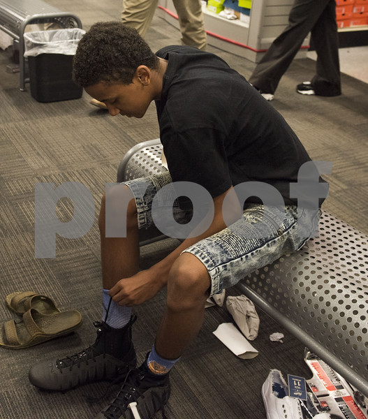 Kid tries on shoes at Academy