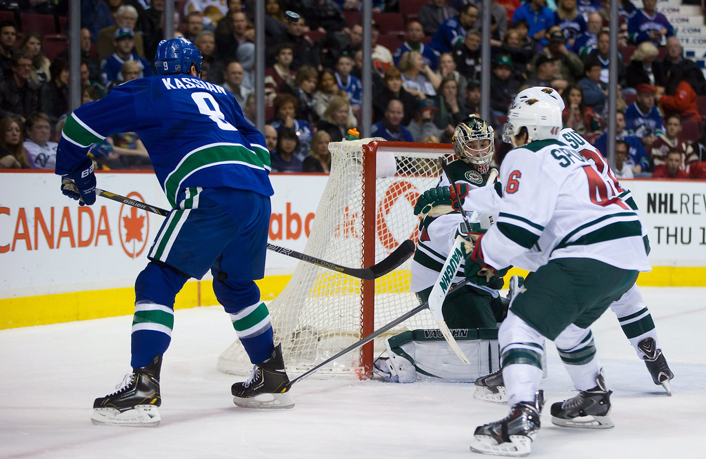 . Vancouver Canucks\' Zack Kassian, left, has his shot deflect off the side of the net and stay out of the goal as Minnesota Wild goalie Darcy Kuemper, centrt, and Marco Scandella watch during the first period of an NHL hockey game Friday, Feb. 28, 2014, in Vancouver, British Columbia. (AP Photo/The Canadian Press, Darryl Dyck)