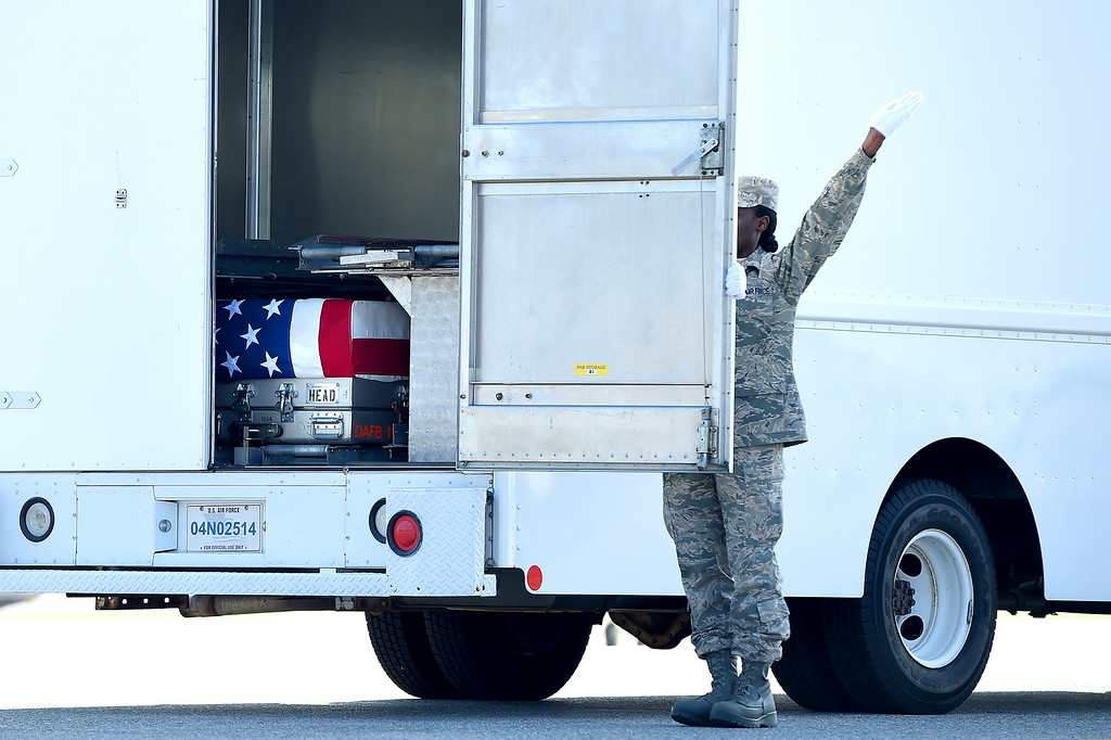 . U.S. Air Force Door Attendant Senior Airman Kristina C. Barr, shuts the door of the transfer vehicle, as the flag-draped transfer case containing the remains of U.S. Army Maj. Gen. Harold J. Greene rest inside during a dignified transfer at Dover Air Force Base on August 7, 2014 in Dover, Delaware.  (Photo by Patrick Smith/Getty Images)