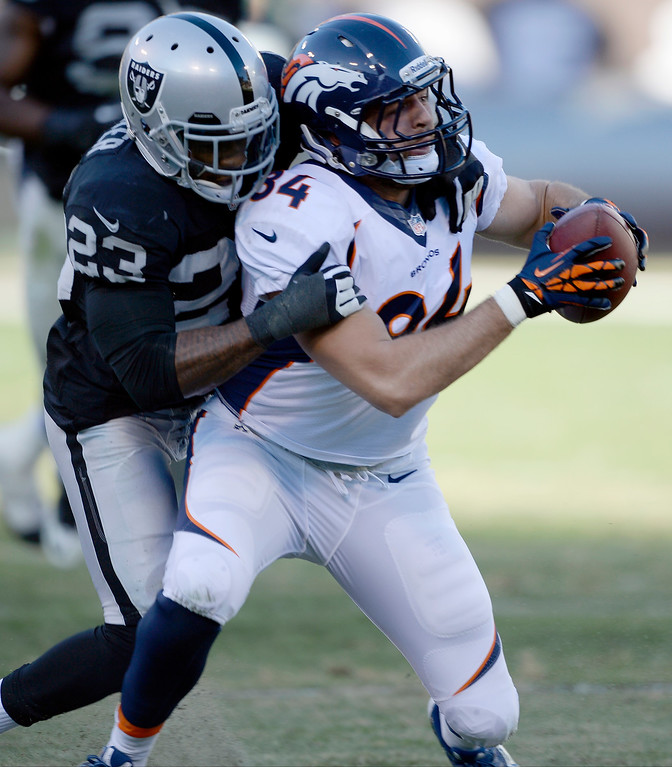 . Denver Broncos tight end Jacob Tamme (84) gets caught from behind by Oakland Raiders cornerback Tracy Porter (23) after a short gain during the third quarter at O.co Coliseum. (Photo by John Leyba/The Denver Post)