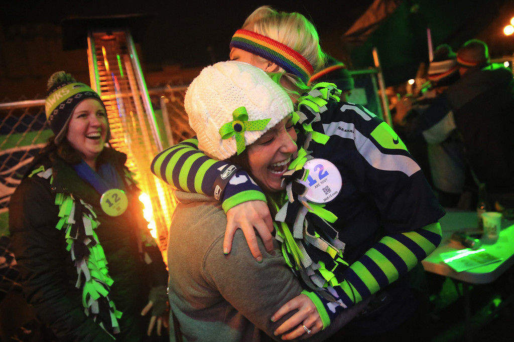 . Monica Atkinson, left, hugs Stephanie Powell. right,at Fuel Sports Bar in the third quarter playing in the Super Bowl against the Denver Broncos in Seattle Sunday, Feb. 2, 2013.(AP Photo/The Seattle Times, Lindsey Wasson)