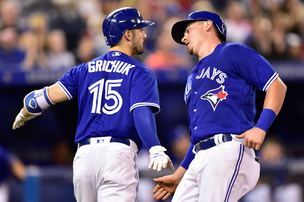 . Toronto Blue Jays Reese McGuire, right,  is congratulated by teammate Randal Grichuk, left, after scoring a run against the Cleveland Indians during third inning American League baseball action in Toronto, Sunday, Sept. 9, 2018. (Frank Gunn /The Canadian Press via AP)