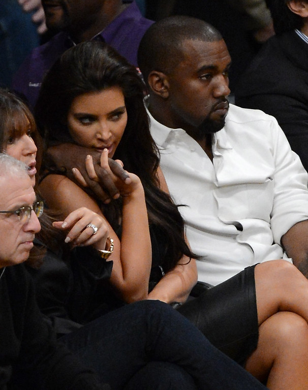 . LOS ANGELES, CA - MAY 12:  Kanye West puts his arm around Kim Kardashian from their courtside seats as the Los Angeles Lakers take on the Denver Nuggets in Game Seven of the Western Conference Quarterfinals in the 2012 NBA Playoffs on May 12, 2012 at Staples Center in Los Angeles, California.  (Photo by Kevork Djansezian/Getty Images)