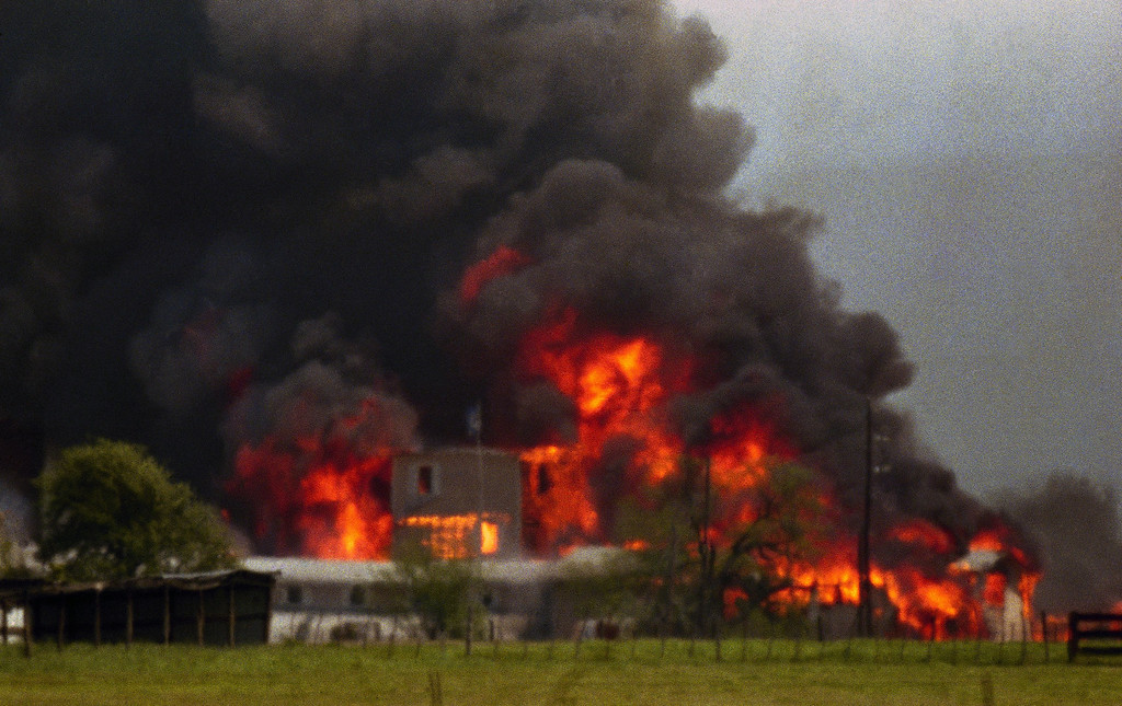 . Fire engulfs the Branch Davidian compound near Waco, Texas on Monday, April 19, 1993. The compound burned to the ground after FBI agents in an armored vehicle smashed the buildings and pumped in tear gar. The Justice Department said cult members set the fire. (AP Photo/Ron Heflin)