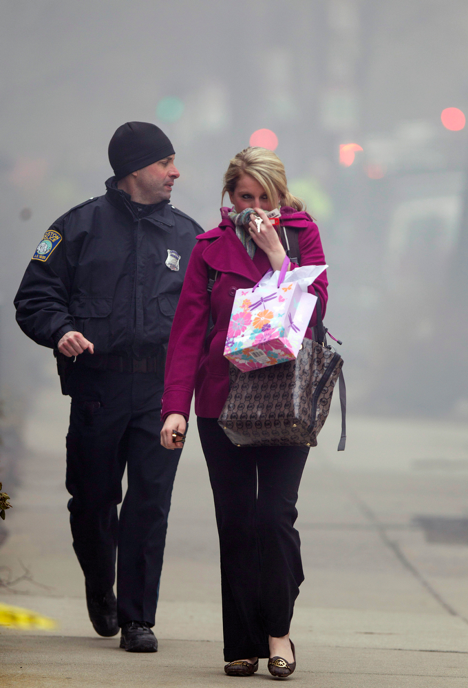 . A Boston Police officer escorts a woman away from the scene of a multi-alarm fire at a four-story brownstone in the Back Bay neighborhood near the Charles River, Wednesday, March 26, 2014, in Boston. Boston EMS spokesman Nick Martin says four people, including at least three firefighters, have been taken to hospitals. (AP Photo/Scott Eisen)