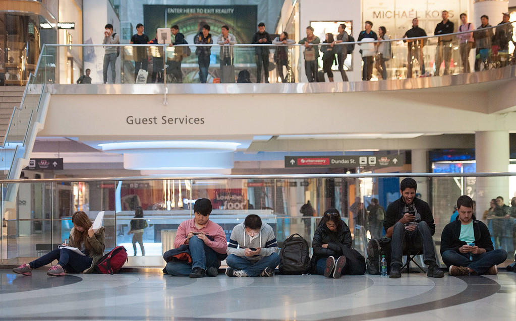. People wait in line to buy the new iPhone 6 at the Eaton Centre in Toronto,  on Friday, Sept. 19, 2014. It is estimated more than a thousand people were in line for the release of the new iPhone 6. (AP Photo/The Canadian Press,Hannah Yoon)