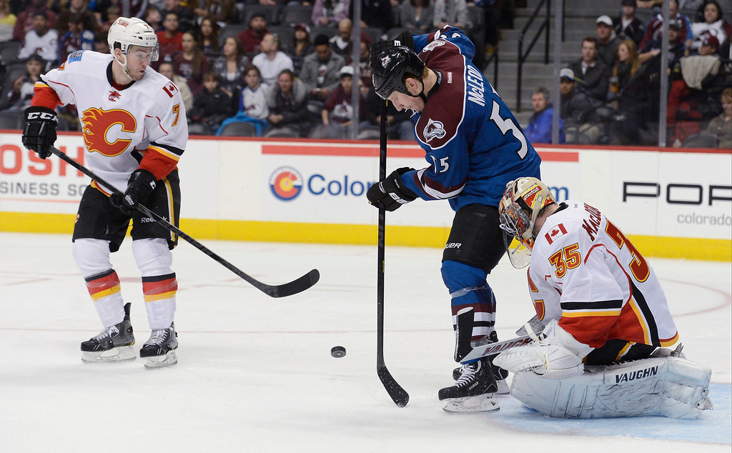. Cody McLeod (55) of the Colorado Avalanche attempts to redirect a shot as Joey MacDonald (35) of the Calgary Flames makes the save during the second period April 8, 2013 at Pepsi Center. (Photo By John Leyba/The Denver Post)
