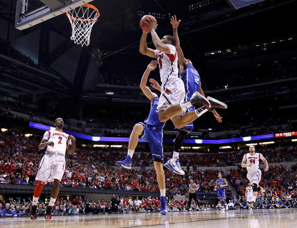 . Louisville Cardinals guard/forward Wayne Blackshear (20) goes to the basket past Duke Blue Devils guard Quinn Cook (2) and Mason Plumlee during their Midwest Regional NCAA men\'s basketball game in Indianapolis, Indiana, March 31, 2013. REUTERS/Jeff Haynes