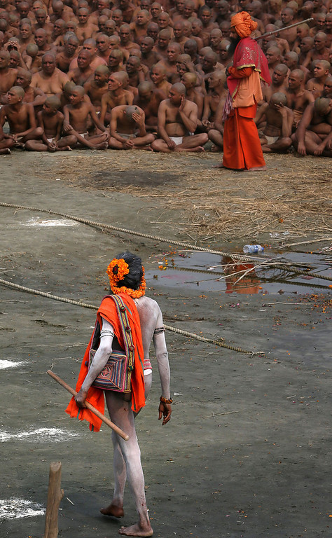 """. A Naga Sadhu, foreground, walks past Hindu holy men of the Juna Akhara sect participate in rituals that are believed to rid them of all ties in this life and dedicate themselves to serving God as a \""""Naga\"""" or naked holy men, at Sangam, the confluence of the Ganges and Yamuna River during the Maha Kumbh festival in Allahabad, India, Wednesday, Feb. 6, 2013. The significance of nakedness is that they will not have any worldly ties to material belongings, even something as simple as clothes. This ritual that transforms selected holy men to Naga can only be done at the Kumbh festival.(AP Photo /Manish Swarup)"""