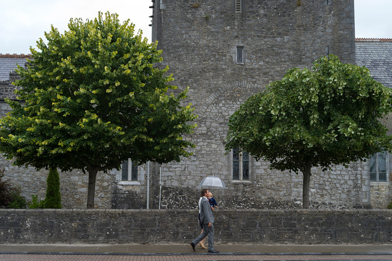 Couple walking with their baby in front of Holy Trinity Abbey Church, Adare, County Limerick, Republic of Ireland
