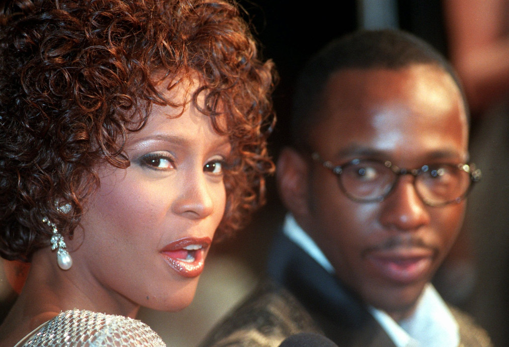 ". Whitney Houston looks over her shoulder as her husband Bobby Brown looks to her at the premiere of ""The Wonderful World of Disney\"" movie \""Cinderella,\"" at Mann\'s Chinese Theater in the Hollywood section of Los Angeles, Monday, Oct. 13, 1997.  (AP Photo/Rene Macura)"
