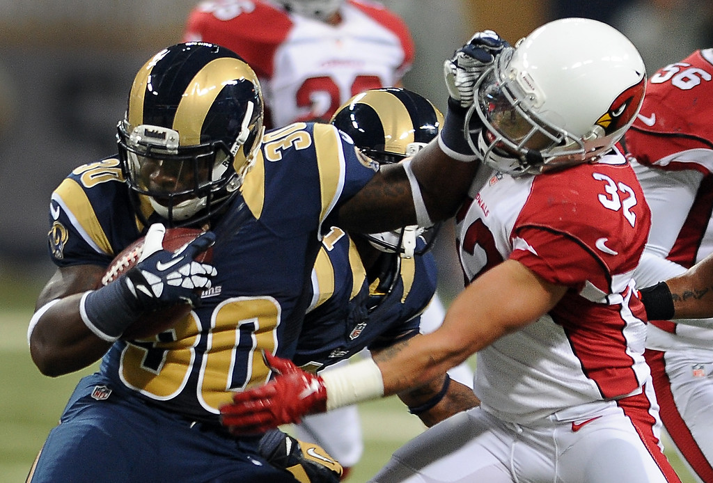 . St. Louis Rams running back Zac Stacy, left, runs with the ball for a 4-yard gain as Arizona Cardinals safety Tyrann Mathieu, right, defends during the second quarter of an NFL football game on Sunday, Sept. 8, 2013, in St. Louis. (AP Photo/L.G. Patterson)