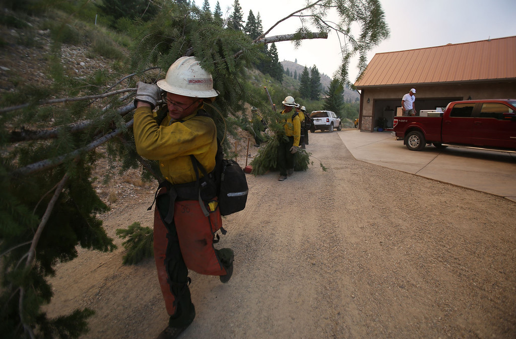 . Firefighters helped residents clear brush around their homes in Pine, Idaho, to protect them from the 80,300-acre Elk Complex Fire burning across Elmore County.    (AP Photo/Times-News,Ashley Smith)  Mandatory  Credit