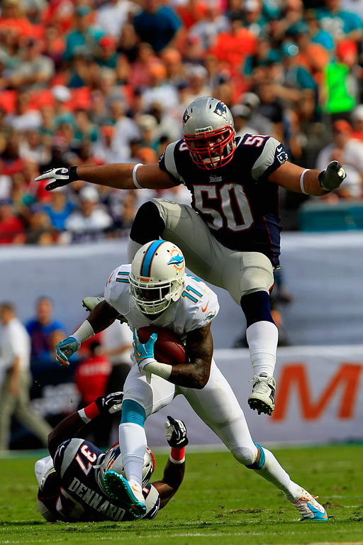 . Mike Wallace #11 of the Miami Dolphins rushes with the ball under pressure from  Rob Ninkovich #50 of the New England Patriots and  Alfonzo Dennard #37 of the New England Patriots at Sun Life Stadium on December 15, 2013 in Miami Gardens, Florida.  (Photo by Chris Trotman/Getty Images)