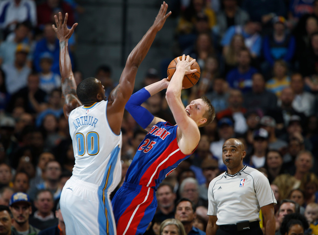 . Detroit Pistons forward Kyle Singler, right, tries to shoot the ball over Denver Nuggets forward Darrell Arthur in the third quarter of the Nuggets\' 89-79 victory in an NBA basketball game in Denver on Wednesday, Oct. 29, 2014. (AP Photo/David Zalubowski)