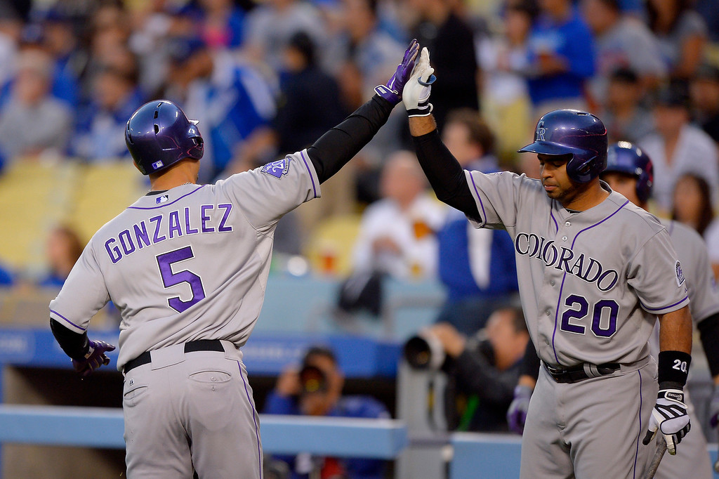 . Colorado Rockies\' Carlos Gonzalez, left, is congratulated by Wilin Rosario after scoring on a sacrifice fly by Michael Cuddyer during the first inning of their baseball game against the Los Angeles Dodgers, Wednesday, May 1, 2013, in Los Angeles. (AP Photo/Mark J. Terrill)