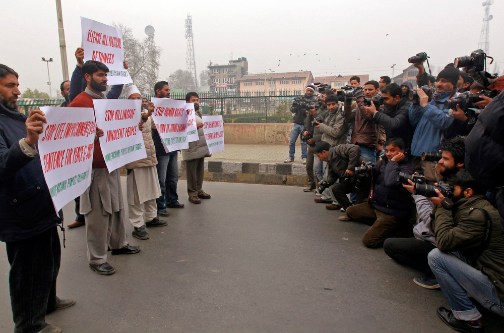 Description of . Members of the media take pictures of activists of a separatist party, Jammu Kashmir Freedom League, carrying placards, during a protest to mark the International Human Rights Day, in Srinagar December 10, 2012. Many demonstrations, in addition to this one, were held in Srinagar on Monday by non-governmental organisations, separatist groups and a Kashmiri lawmaker to mark International Human Rights Day. REUTERS/Fayaz Kabli
