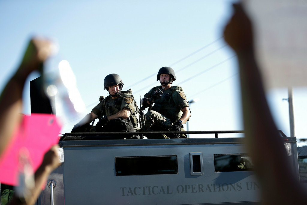 . Police in riot gear watch protesters in Ferguson, Mo. on Wednesday, Aug. 13, 2014. On Saturday, Aug. 9, 2014, a white police officer fatally shot Michael Brown, an unarmed black teenager, in the St. Louis suburb. (AP Photo/Jeff Roberson)