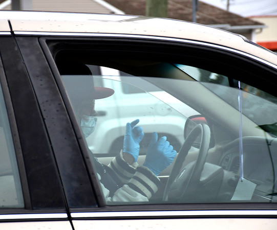 3/20/2020 Mike Orazzi | Staff A driver wearing a mask and gloves while driving on Middle Street in Bristol on Friday.