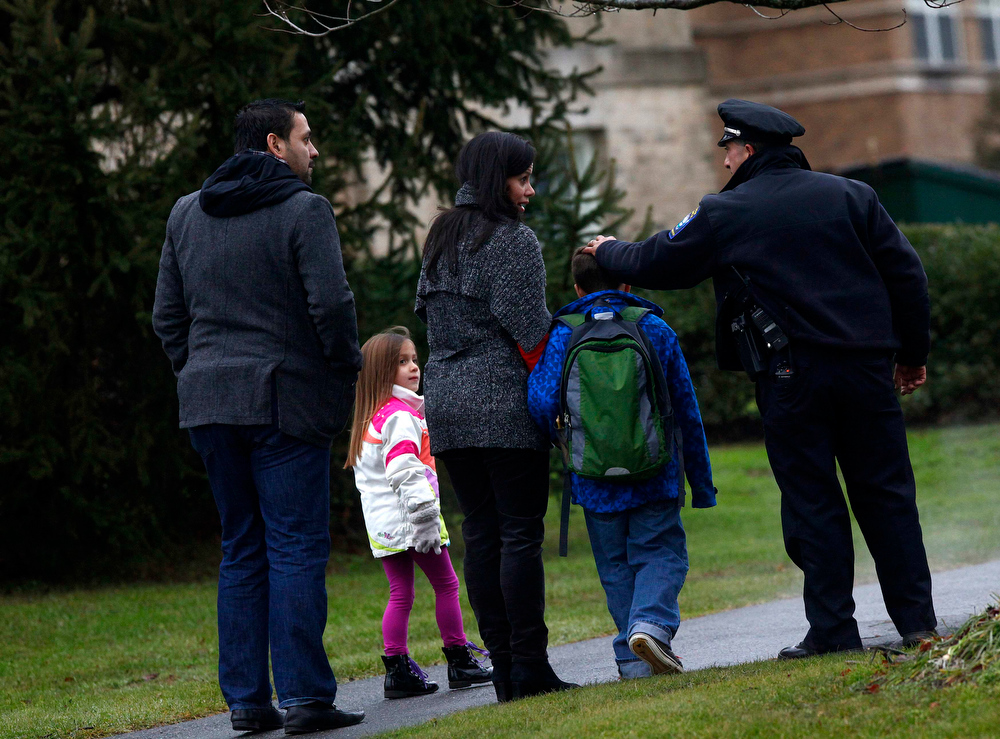 . Easton police officer J. Sollazzo talks to parents dropping off a child coming to school in Newtown, Connecticut December 18, 2012. The schools of Newtown, which stood empty in the wake of a shooting rampage that took 26 of their own, will again ring with the sounds of students and teachers on Tuesday as the bucolic Connecticut town struggles to return to normal. REUTERS/Eric Thayer