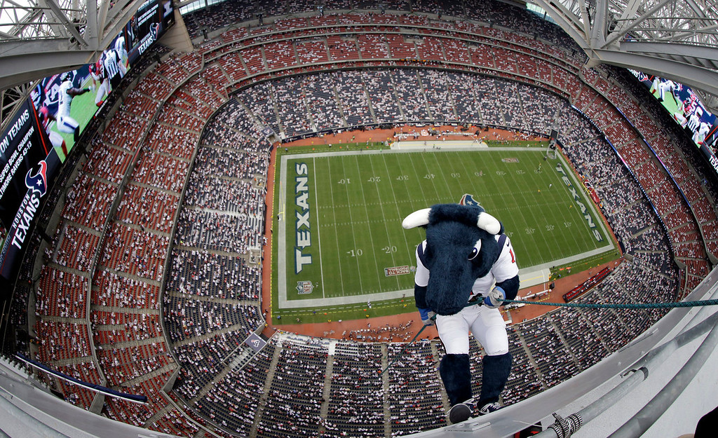 . Toro, the Houston Texans mascot, lowers himself into Reliant Stadium to help introduce the team\'s AFC South division banner before an NFL football game against the Tennessee Titans, Sunday, Sept. 15, 2013, in Houston. (AP Photo/David J. Phillip)