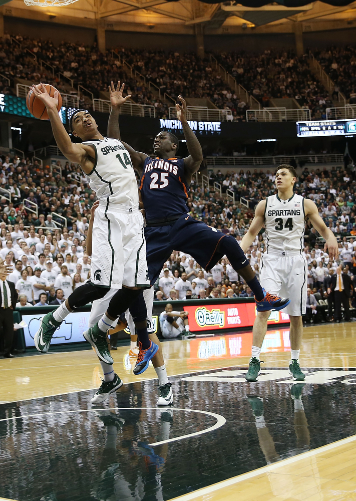. Gary Harris #14 of the Michigan State Spartans and Kendrick Nunn #35 of the University of Illinois fight for ball control during the first half of the game at Breslin Center on March 1, 2014 in East Lansing, Michigan.  (Photo by Leon Halip/Getty Images)