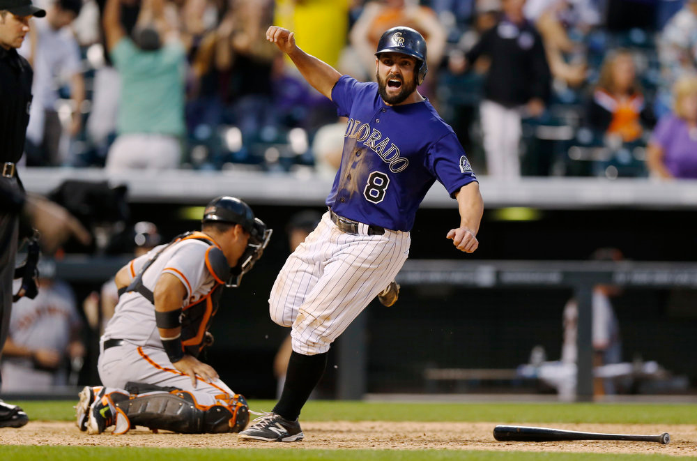 . Colorado Rockies\' Michael McKenry, right, celebrates as he scores the go-ahead run on a single by Charlie Blackmon as San Francisco Giants catcher Guillermo Quiroz looks on in the ninth inning of the Rockies\' 10-9 victory in a baseball game in Denver on Monday, Sept. 1, 2014. (AP Photo/David Zalubowski)