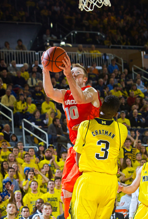. Syracuse guard Trevor Cooney (10) attempts to make a basket over Michigan guard Kameron Chatman (3), in the second half of an NCAA college basketball game at Crisler Center in Ann Arbor, Mich., Tuesday, Dec. 2, 2014. (AP Photo/Tony Ding)