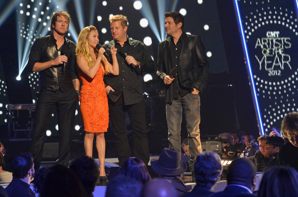 Description of . Hosts Hayden Panettiere and Rascal Flatts speak onstage during the 2012 CMT Artists Of The Year at The Factory at Franklin on December 3, 2012 in Franklin, Tennessee.  (Photo by Rick Diamond/Getty Images for CMT)