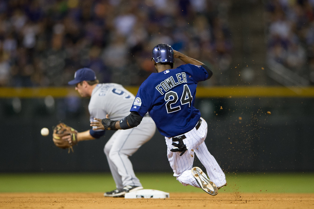 . Dexter Fowler #24 of the Colorado Rockies slides safely into second base as Jedd Gyorko #9 of the San Diego Padres receives the throw on a fly out in the fourth inning of a game at Coors Field on August 12, 2013 in Denver, Colorado. A rain delay was called in the eighth inning with the Rockies leading 8-1.  (Photo by Dustin Bradford/Getty Images)