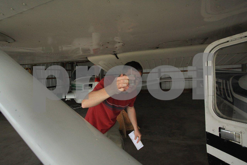 Young civilian pilot performing his pre-flight on a Cessna by checking the fuel.