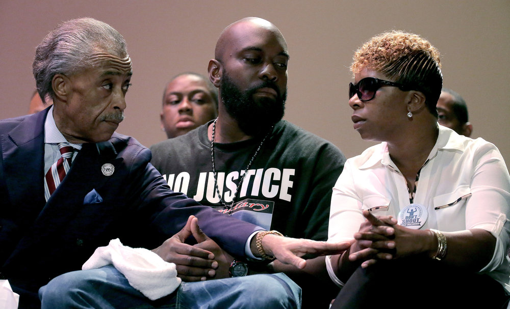 . Rev. Al Sharpton speaks with parents of Michael Brown, Michael Brown Sr. and Lesley McSpadden during a rally at Greater Grace Church, Sunday, Aug. 17, 2014, for their son who was killed by police last Saturday in Ferguson, Mo. Brown\'s shooting in the middle of a street, following a suspected robbery of a box of cigars from a nearby market, has sparked a week of protests, riots and looting in the St. Louis suburb. (AP Photo/Charlie Riedel)