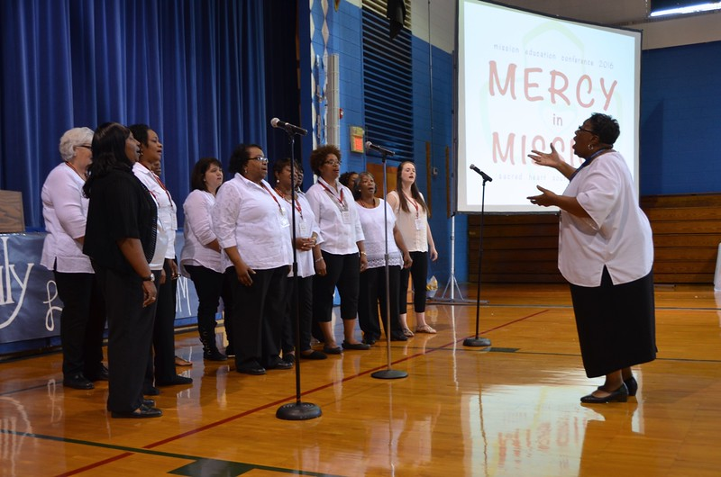 Clara Isom, principal of Holy Family, and the choir made up of teachers and staff of the school, lead the conference participants in song.