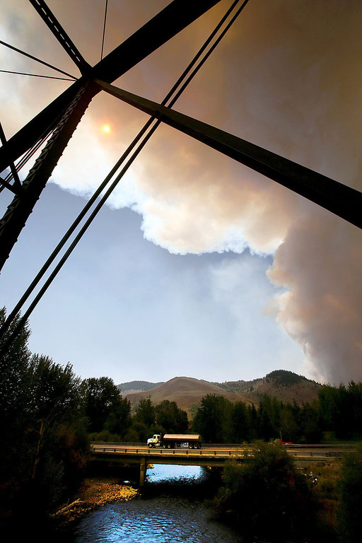 . A view from a bridge over the Big Wood River, as smoke rises from the 44,000 acre Beaver Creek Fire on Thursday, Aug. 15, 2013 north of Hailey, Idaho. Evacuations are in place for residents on Deer Creek Road and on Green Horn Gulch Road west of Idaho Highway 75 north of Hailey, Idaho. (AP Photo/Times-News, Ashley Smith)