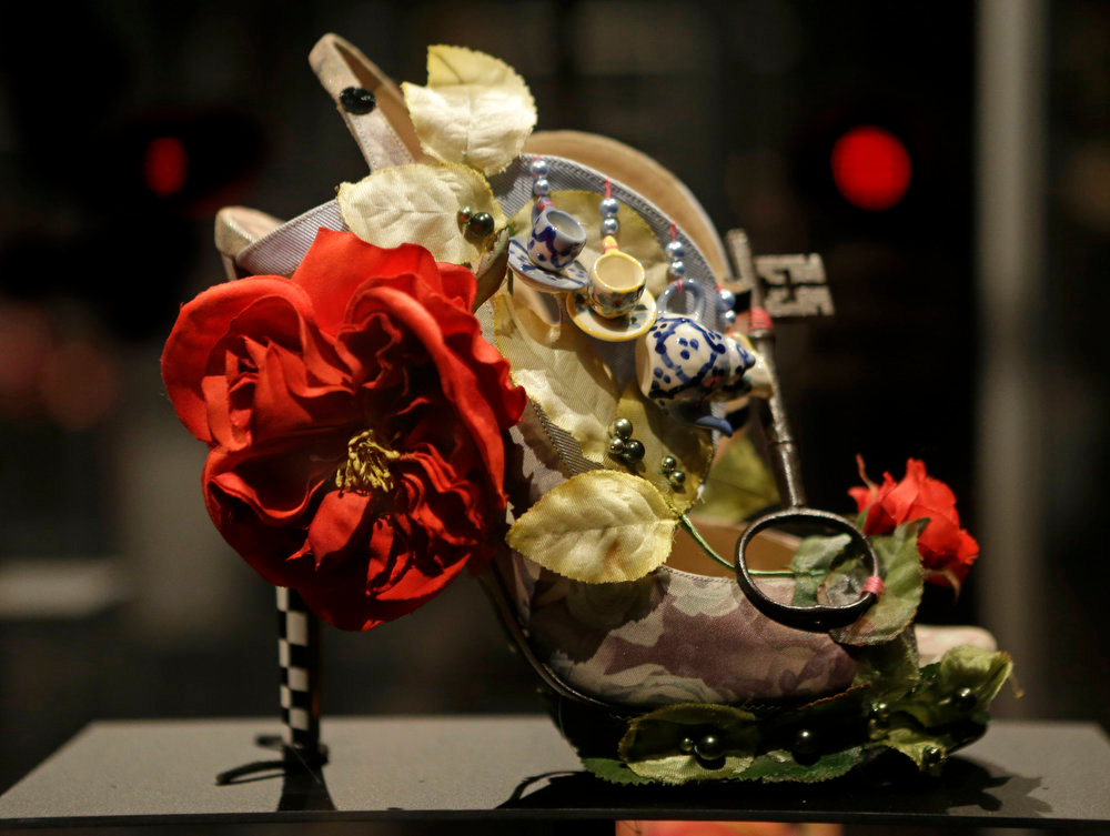 Description of . A shoe decorated with a miniature tea set and a lock titled