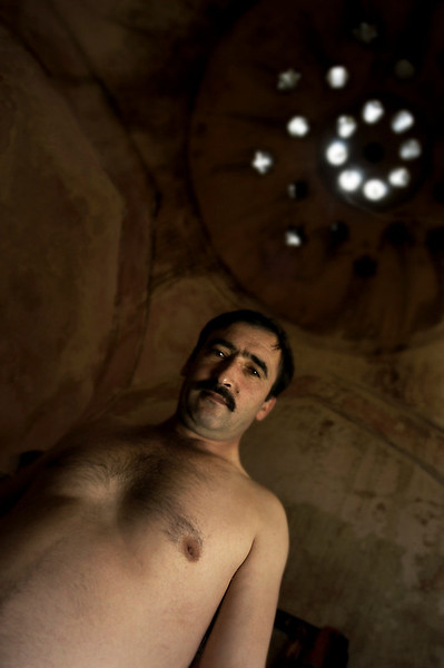 A person taking a Turkish bath first relaxes in a room (known as the warm room) that is heated by a continuous flow of hot, dry air allowing the bather to perspire freely. Bathers may then move to an even hotter room (known as the hot room) before splashing themselves with cold water. After performing a full body wash and receiving a massage, bathers finally retire to the cooling-room for a period of relaxation.  Masseuse, Istanbul, 2009