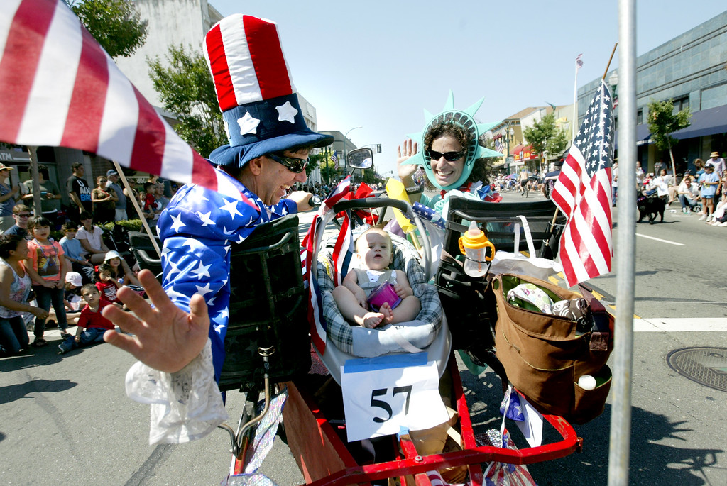 . Benjamin James, left, and his wife Ellen and their 15-month-old daughter Ruby take part in the Alameda Mayor\'s July 4th Parade on Park Street in Alameda, Calif., on Thursday, July 4, 2013. (Ray Chavez/Bay Area News Group)