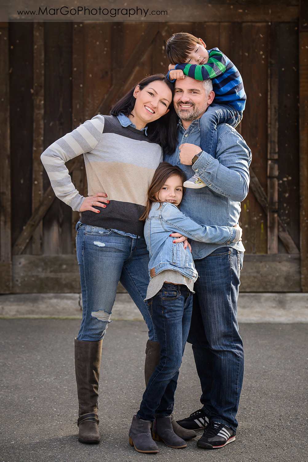 full body vertical portrait of family of 4 in blue and grey clothes mother standing next to father holding a sleeping boy on a piggybackand dauther in the middle during photo session at Old Borges Ranch in Walnut Creek