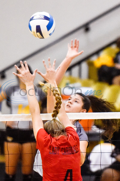 Trinity Valley Community College's Erica Airheart (4) jumps to block the ball as Tyler Junior College's Breeana Gamueda (8) spikes the ball during a college volleyball game at Tyler Junior College in Tyler, Texas, on Wednesday, Sept. 19, 2018. (Chelsea Purgahn/Tyler Morning Telegraph)