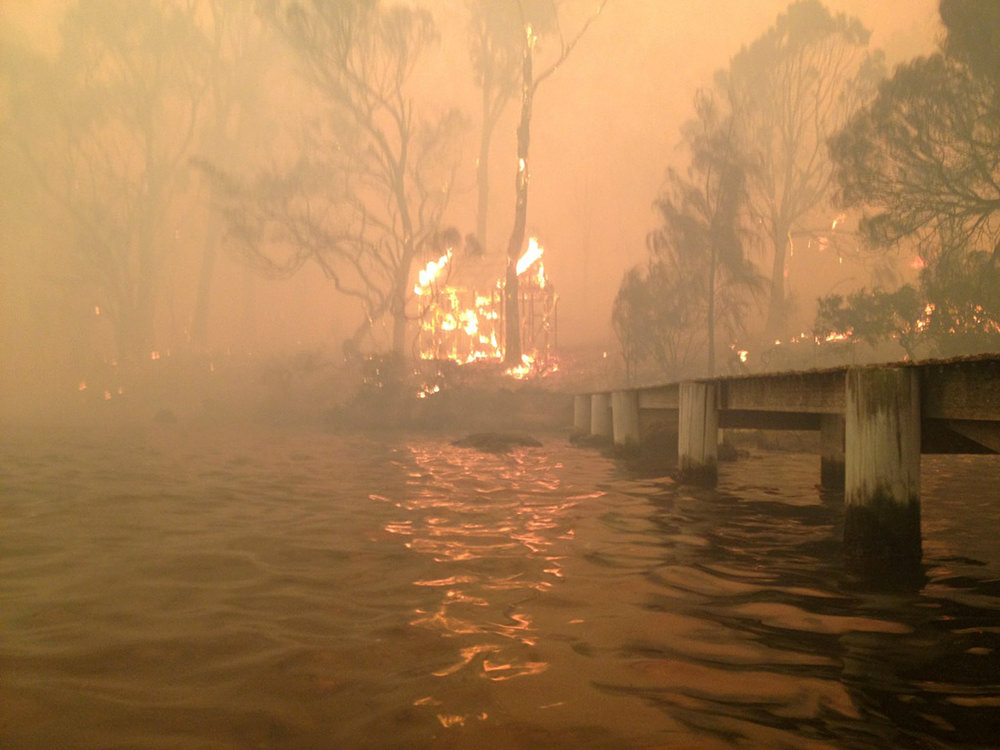 . In this Jan. 4, 2013, photo provided by the Holmes family, a building burns near a jetty where Tim and Tammy Holmes attempt to shelter their five grandchildren as a wildfire rages nearby in the Tasmanian town of Dunalley, east of the state capital of Hobart, Australia. The family credits God with their survival from the fire that destroyed around 90 homes in Dunalley. Record temperatures across southern Australia cooled Wednesday, Jan. 9, 2013, reducing the danger from scores of raging wildfires but likely bringing only a brief reprieve from the summer\'s extreme heat and fire risk.  (AP Photo/Holmes Family, Tim Holmes)