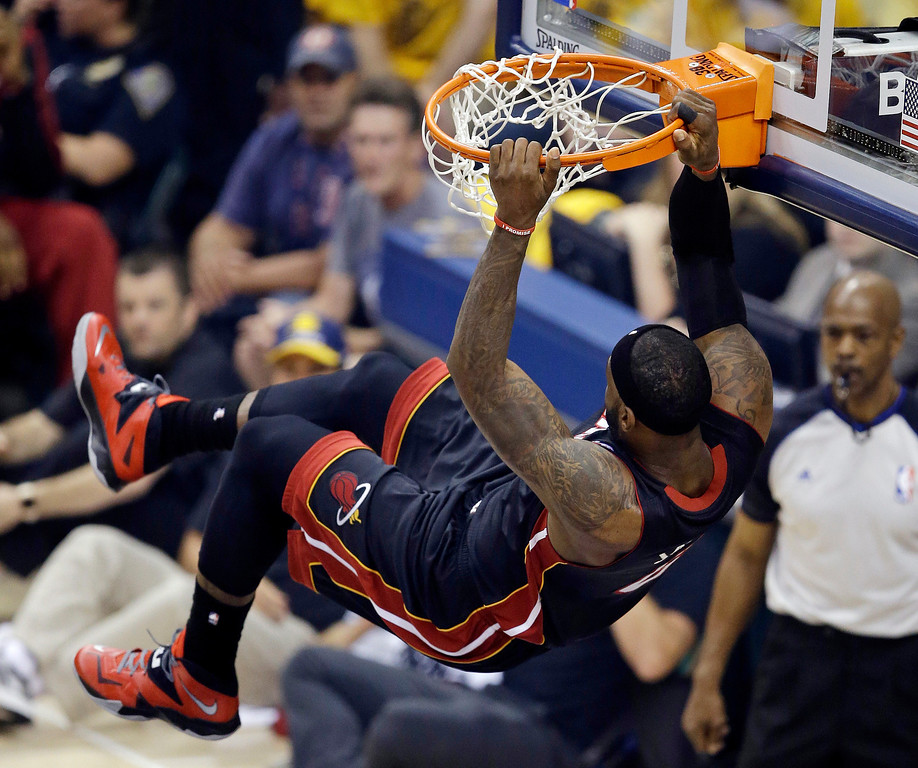 . Miami Heat\'s LeBron James hangs from the rim following a dunk during the first half of Game 5 of the Eastern Conference finals NBA basketball playoff series against the Indiana Pacers, on Wednesday, May 28, 2014, in Indianapolis. (AP Photo/Darron Cummings)