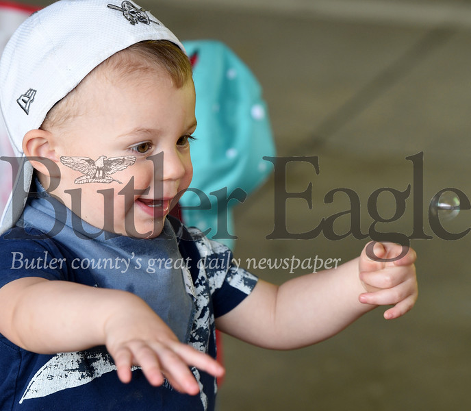 Harold Aughton/Butler Eagle: Van Matonak, 2, of Butler chases the bubble his grandfather, Bob Dandoy, created on the opening day of the City of Butler Farmers' Market. The market will be open every Saturday, from 8:00 a.m. - 1:00 p.m. through the end of October.