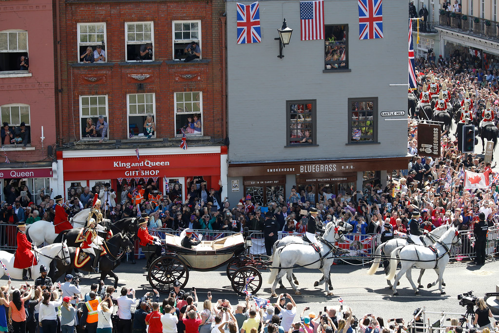 . Well-wishers lining the streets wave and cheer as Britain\'s Prince Harry, Duke of Sussex and his wife Meghan Markle, Duchess of Sussex pass riding in the Ascot Landau Carriage during their carriage procession on Castle Hill outside Windsor Castle in Windsor, near London, England, Saturday, May 19, 2018. (Odd Andersen/pool photo via AP)