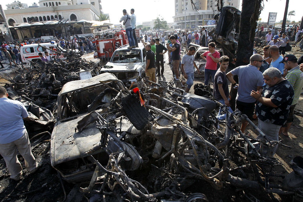 . Lebanese civilians gather next to the site of a blast outside the Al-Taqwamosque in the northern city of Tripoli on August 23, 2013.  AFP PHOTO/ANWAR  AMRO/AFP/Getty Images