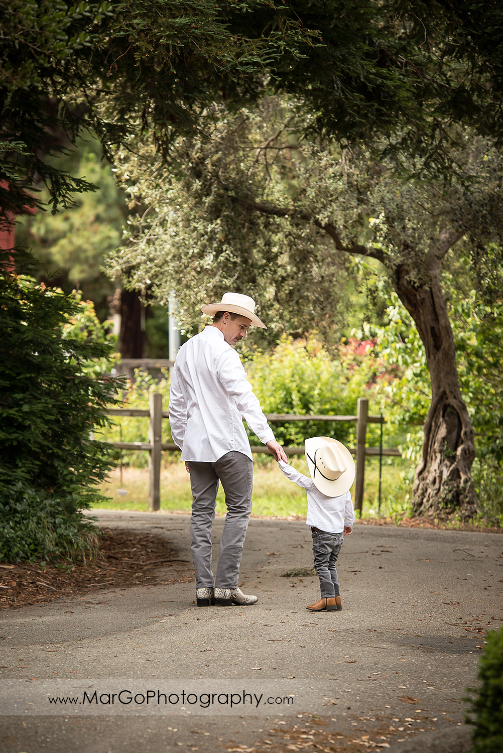 man and little boy in white shirts, gray jeans and cowboy hats walking down the aisle in Shinn Historical Park and Arboretum in Fremont