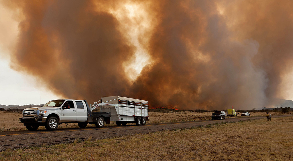 . Residents evacuate along Hays Road in Peeples Valley, Ariz. as the Yarnell Hill Fire advances on Sunday, June 30, 2013. The fire started Friday and picked up momentum as the area experienced high temperatures, low humidity and windy conditions. It has forced the evacuation of residents in the Peeples Valley area and in the town of Yarnell. (AP Photo/The Arizona Republic, Tom Story)