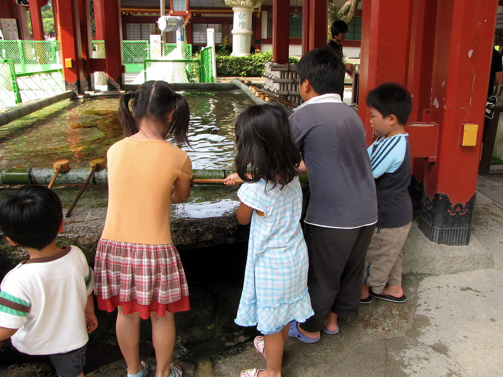 Kids cleansing themselves before entering the temple