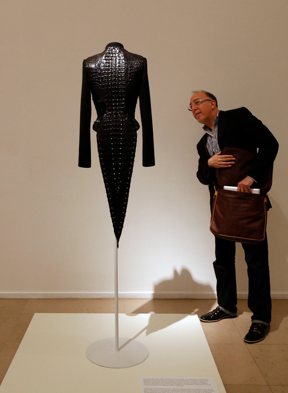 """. A visitor looks at \""""Swallow-tailed jacket of wool cloth and crocodile\"""" of Haute Couture Spring Summer 2003 collections by French Tunisian born Fashion designer Azzedine Alaia, presented for the first Paris retrospective of couturier at the Museum of Modern Art in Paris, Wednesday, Sept. 25, 2013. A selection of seventy iconic models retracing a unique creative career of Alaia are displayed for the reopening of the Galliera Museum and in the Matisse room at the Museum of Modern Art of Paris. (AP Photo/Francois Mori)"""