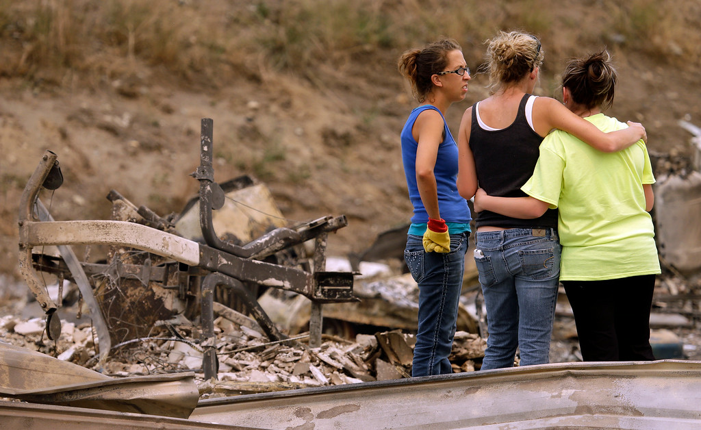 . A group of women pause after sifting through the rubble of a four-plex apartment building destroyed in a wildfire the night before Friday, July 18, 2014, in Pateros, Wash. A fire racing through rural north-central Washington destroyed about 100 homes, leaving behind smoldering rubble, solitary brick chimneys and burned-out automobiles as it blackened hundreds of square miles. Friday\'s dawn revealed dramatic devastation, with the Okanagan County town of Pateros, home to 650 people, hit especially hard. (AP Photo/Elaine Thompson)